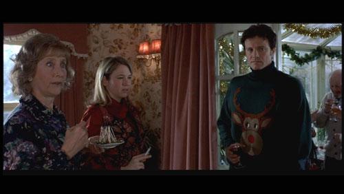 """Colin Firth à droite de l'image, porte un pull moche """"tête de renne"""" dans le journal de Bridget Jones"""